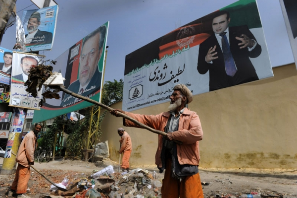 Afghan municipality workers clear garbage in front of parliamentary election campaign billboards of various candidates in Kabul on September 6, 2010. (Shah Marai/AFP/Getty Images)