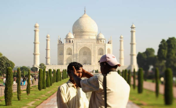 A photographer poses a tourist the Taj Mahal on September 29, 2010 in Agra, India.