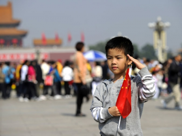 A boy poses for pictures on Tiananmen Square in Beijing on September 30, 2010, on the eve of China's National Day.