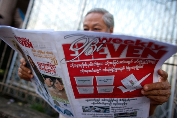 A man reads a newspaper promoting elections on November 5, 2010 in Yangon, Burma. (CKN/Getty Images)