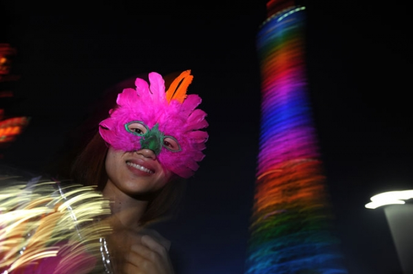 A mask seller stands outside as Caton tower illuminates during a light show rehersal for the opening ceremony for the 16th Asian Games, in Guangzhou on November 10, 2010.