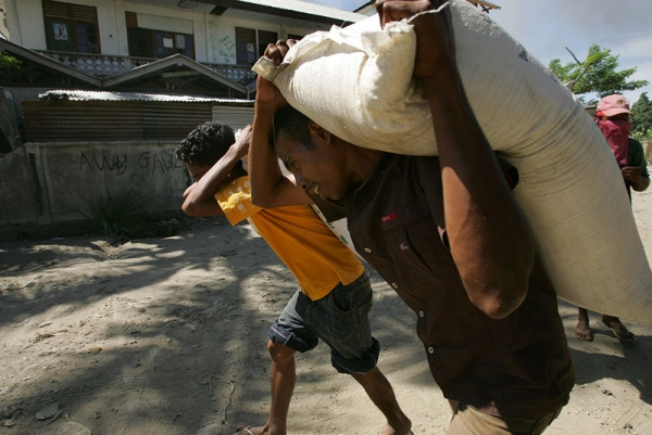 East Timorese residents of Dili haul bags of rice as they loot empty homes during political turmoil in Dili, East Timor, in 2006. (Paula Bronstein/Getty Images)