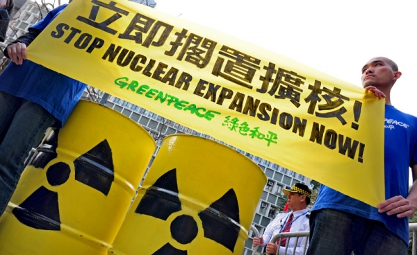 Members of environmental action group Greenpeace hold up an anti-nuclear banner in front of the Central Government offices in Hong Kong on March 22, 2011. (RICHARD A. BROOKS/AFP/Getty Images)