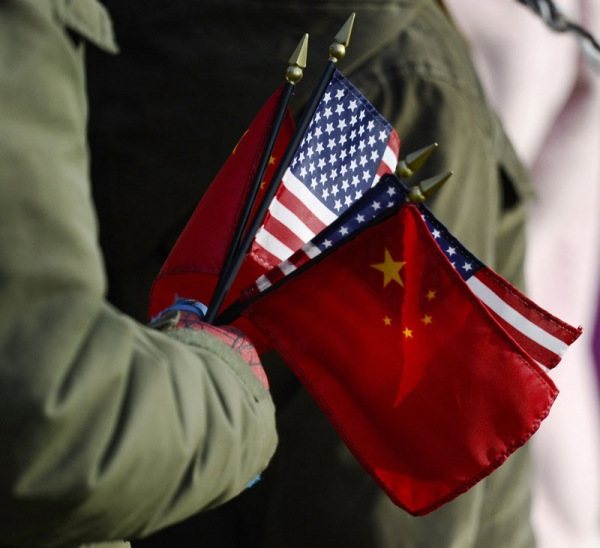 An onlooker holds the US and China flags as US President Barack Obama welcomes Chinese President Hu Jintao during a State Arrival ceremony on the South Lawn of the White House in Washington, DC, January 19, 2011. (Jewel Samad/AFP/Getty Images)