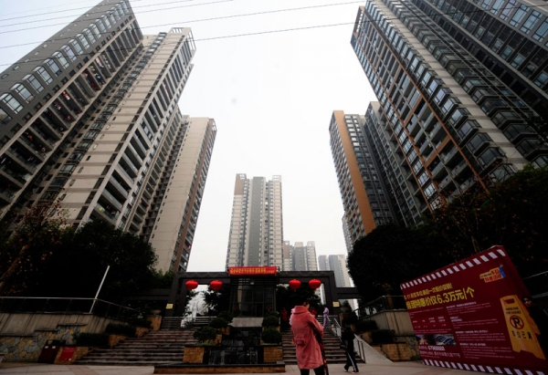Pedestrians pass a courtyard between high-rise apartments in southwest China's Chongqing municipality on January 28, 2011. (STR/AFP/Getty Images)