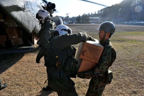 Chief Naval Air Crewman Francisco Garcia (L) delivers meals ready-to-eat to a Japanese Ground Self-Defense Force soldier on Mar. 18, 2011 in Yamada, Japan. (Lt. Eric Quarlesr/US Navy via Getty Images)