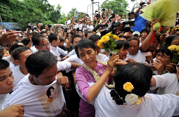 Myanmar's democracy icon Aung San Suu Kyi (C) walks through a crowd of supporters and reporters as she arrives for celebrations of her 66th birthday at the National League for Democracy (NLD) headquarters in Yangon on June 19, 2011. (Soe Than Win/AFP/Getty Images)