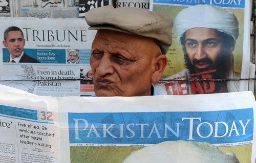 A Pakistani man reads a newspaper with the front page displaying news of the death of Osama bin Laden at a stall in Lahore on May 3, 2011. (Arif Ali/AFP/Getty Images)