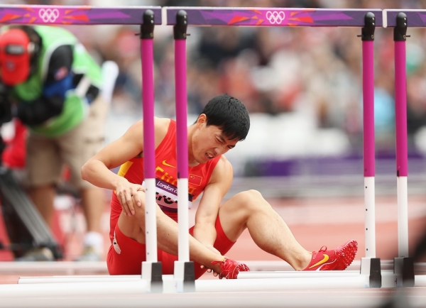 Liu Xiang of China sits on the track after getting injured in the Men's 110m Hurdles Round 1 Heats on Day 11 of the London 2012 Olympic Games at Olympic Stadium on August 7, 2012 in London, England. (Ezra Shaw/Getty Images)