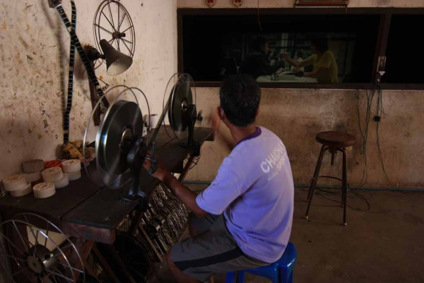The projectionist rewinds a reel of film by hand at the Thai Rama Theater in Uthumphon Pisai District, Sri Saket, Thailand. (Philip Jablon)