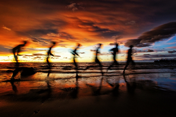 A man runs down the beach in the golden glow of the sun in Labuan, Malaysia on April 13, 2012. (SaturatedEyes/Flickr)