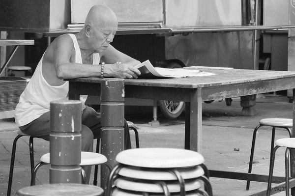 A man reads the morning newspaper in Chinatown, Singapore on September 18, 2012. (beegee49/Flickr)