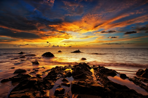 The sun sets over the rocky waters in Labuan, Malaysia on May 28, 2012. (SaturatedEyes/Flickr)