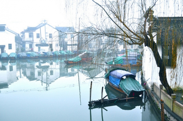 Boats rest under a drooping tree in the still waters of Zhouzhuang, China on January 14, 2013. (Sharon Hahn Darlin/Flickr)