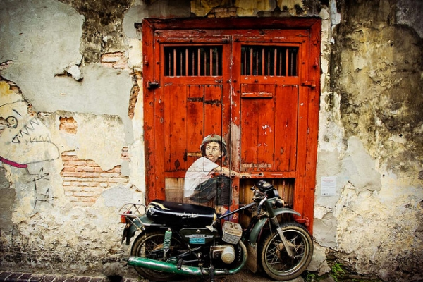 "Ernest Zacharevic leaving his mark with vibrant street art in George Town, Penang. ""Boy on a Bike"" is a mural on the wall along Ah Quee Street. (Catherine Mar)"
