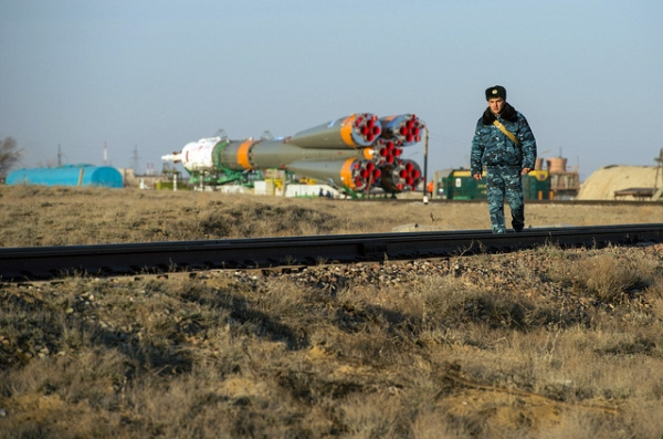 A Russian security guard is seen walking along the train tracks with the Soyuz rocket in the background at the Baikonur Cosmodrome in Kazakhstan on March 26, 2013. (nasa hq photo/Flickr)