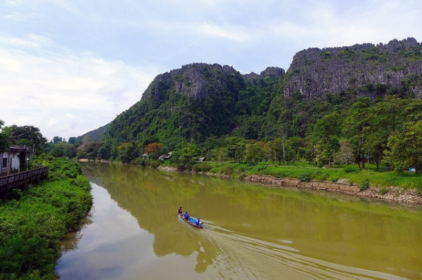 A boat full of people glide smoothly over the waters of the Nam Song river in Vang Vieng, Laos on May 18, 2013. (Madeleine_H/Flickr)