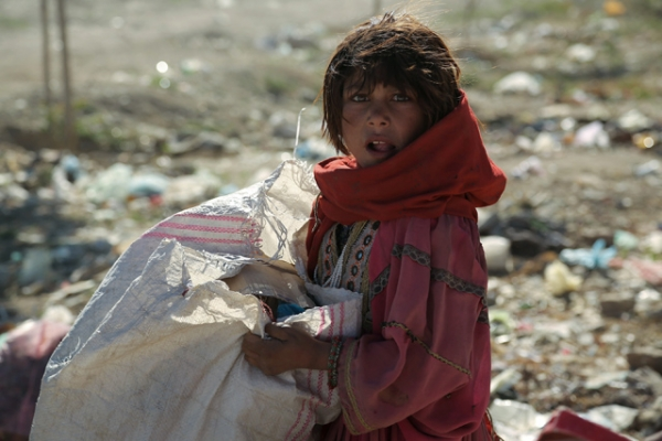 A young nomad girl looks on as she searches amongst the garbage for iron and plastic items to sell in Ghazni, Afghanistan on May 28, 2013. (Rahmatullah Alizada/AFP/Getty Images)