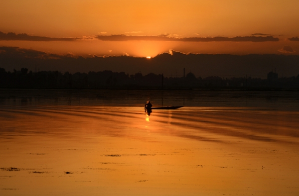 A Kashmiri fisherman paddles his boat during sunset on Dal Lake in Srinagar, India on May 29, 2013. (Tauseef Mustafa/AFP/Getty Images)