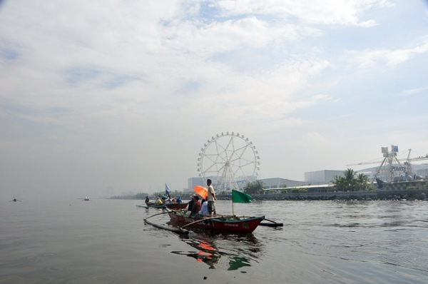 Fishermen cruise serenely through a mall and entertainment park along the bay in Manila, Philippines on May 31, 2013. (Veejay Villafranca/Getty Images))