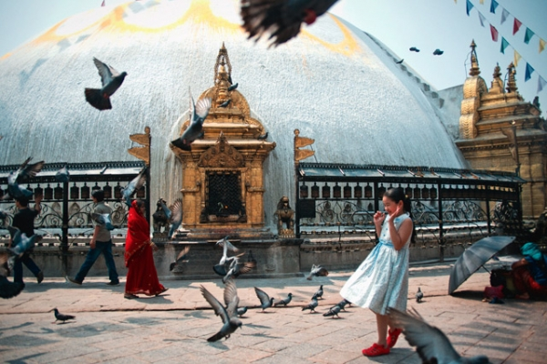 A young girl holds her ground amidst a flock of pigeons in Kathmandu, Nepal on May 10, 2013. (Elliot Scott/Flickr)