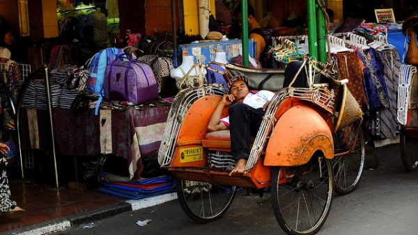 A man reclines in his seat and takes a quick nap alongside a market street in Yogyakarta, Indonesia on June 23, 2013. (Kurniawan Gunadi/Flickr)