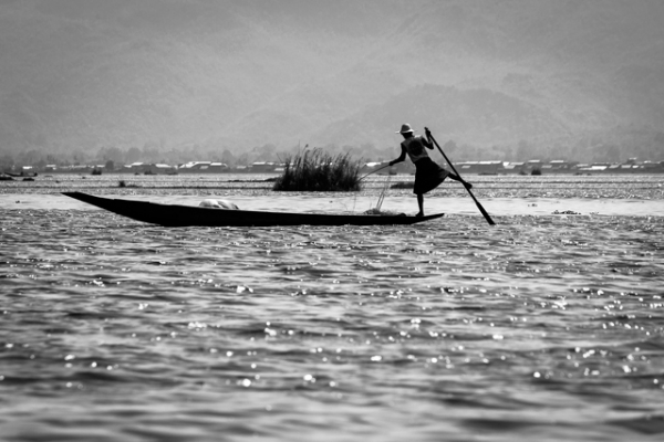 A fisherman balances precariously while rowing with his legs in Nyaung Shwe, Myanmar on May  9, 2013. (Fabio/Flickr)