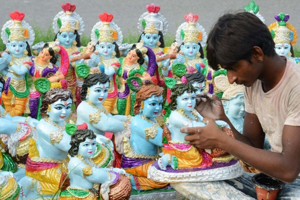Indian artist Suresh amidst statues of the Hindu Lord Krishna at a roadside stall on the outskirts of Amritsar on August 25, 2013. (Narinder Nanu/AFP/Getty Images)