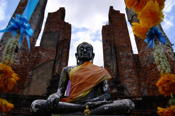 A miniature golden Buddha sits in front of a giant Buddha statue surrounded by old columns in Ayutthaya, Thailand in September 2013. (Daniel Jarrett)