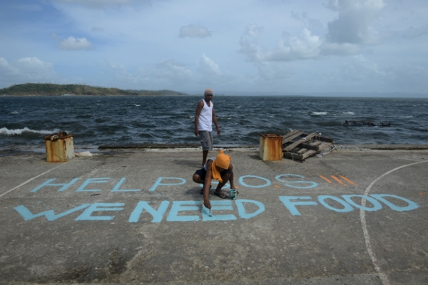 "A man paints a message on a basketball court that reads ""Help SOS We Need Food"" in Tacloban, Philippines after the city was devastated by Super Typhoon Haiyan on November 11, 2013. (Noel Celis/AFP/Getty Images)"