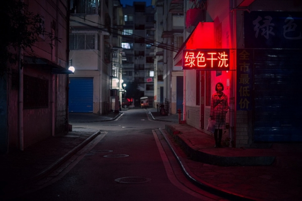 A woman stands under a red neon sign, in an empty street in Guilin, China on November 13, 2013. (金喜 刘/Flickr)