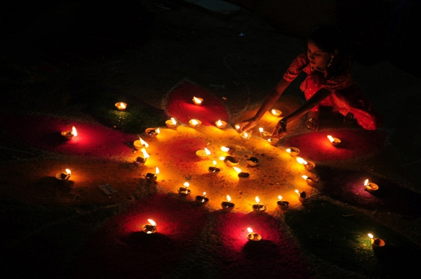 A Pakistani Hindu woman lights an earthen oil lamp in honor of Diwali in Karachi on October 26, 2011. (Rizwan Tabassum/AFP/Getty Images)
