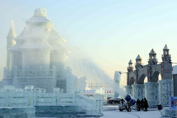 In preparation for China's Ice and Snow World, a snow-making machine covers a sculpture with artificial snow in Harbin, China on January 4, 2014. (Goh Chai Hin/AFP/Getty Images)