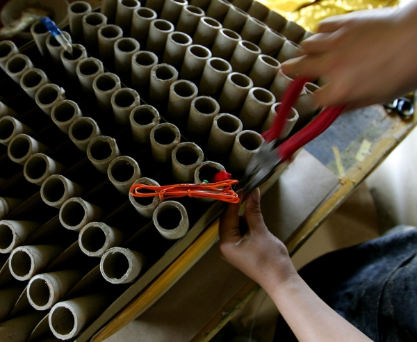 On June 21, 2006, a woman inserts fuses into firework cartridges at Tanghua Factory in Liuyang City, located in the Hunan province of China. (Guang Niu/Getty Images)