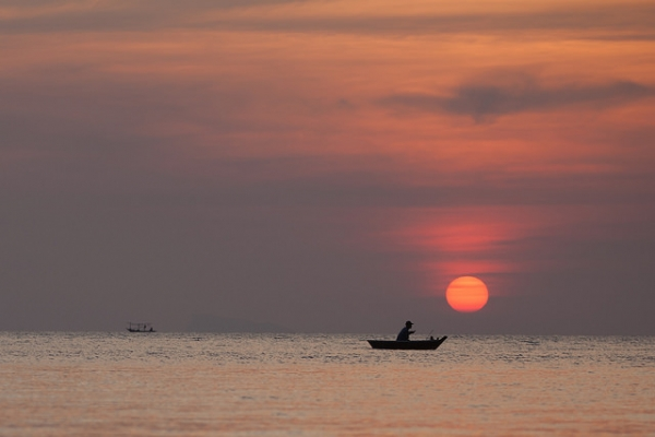 A man in his boat is silhouetted against the setting red sun in Phangan, Thailand on February 18, 2014. (Jens Schott Knudsen/Flickr)