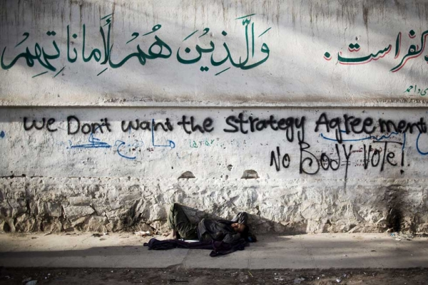 An Afghan homeless man sleeps under graffiti protesting against the upcoming presidential elections and the security agreement with the U.S. in Herat, Afghanistan on March 29, 2014. (Behrouz Mehri/AFP/Getty Images)