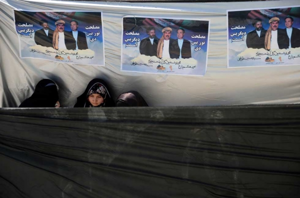 Afghan supporters stand under political posters bearing the image of presidential candidate Gul Agha Sherzai during a political rally on March 30, 2014. (Farshad Usyan/AFP/Getty Images)