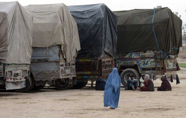 A woman walks past trucks carrying ballot boxes and election material in Kandahar on April 3, 2014. (Banaras Khan/AFP/Getty Images)