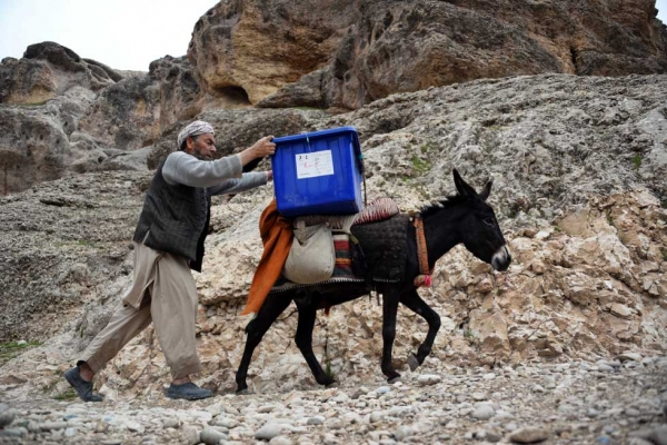 An election worker walks alongside a donkey as he and other workers transport election materials and ballot boxes to remote polling stations in Balkh Province in northern Afghanistan on April 3, 2014. (Farshad Usyan/AFP/Getty Images)