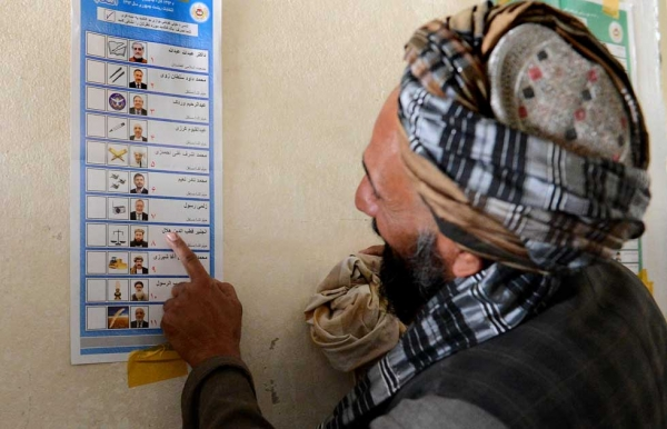 A voter looks at a candidate list prior to casting his vote at a local polling station in Kandahar on April 5, 2014. (Banaras Khan/AFP/Getty Images)