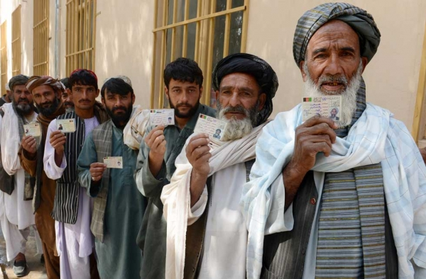 Afghan voters display their national identity cards as they queue to cast their votes at a local polling station in Kandahar on April 5, 2014. (Banaras Khan/AFP/Getty Images)