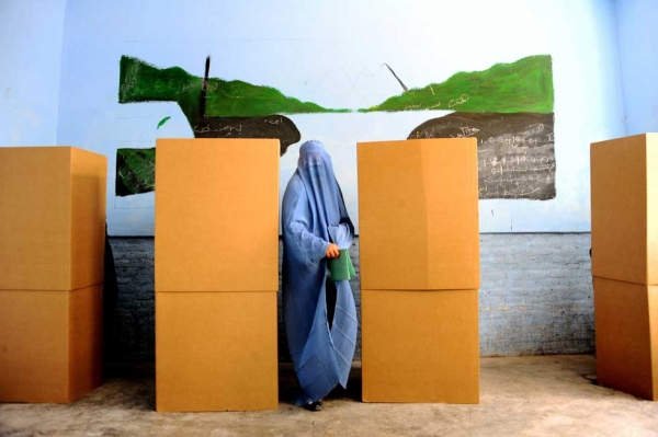 A woman leaves the booth after casting her vote at a polling station in the northwestern city of Herat on April 5, 2014. (Aref Karimi/AFP/Getty Images)