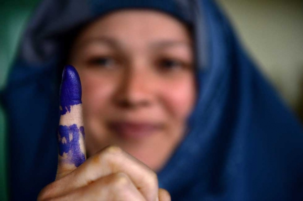 A voter shows her inked finger after she cast her ballot at a local polling station in Kabul on April 5, 2014. (Shah Marai/AFP/Getty Images)