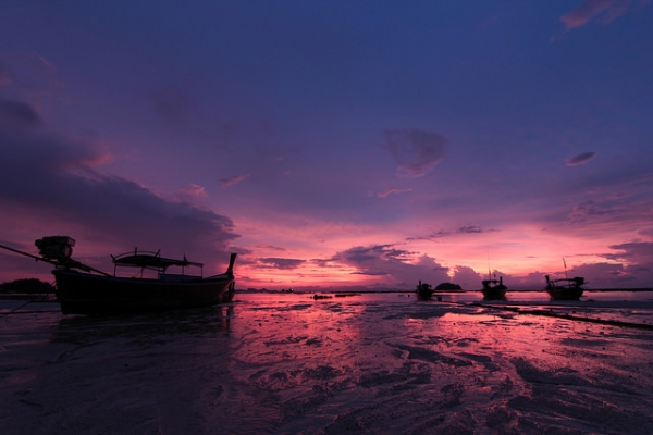 A sunrise over long tail boats paints the sky purple in Koh Lipe, Thailand on April 1, 2014. (Bambi Corro III/Flickr)