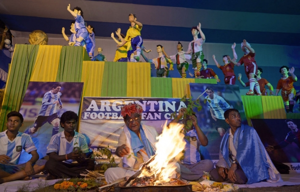 In Kolkata on June 15, 2014, a Hindu priest (C, bottom) performs a special religious prayer organized by Indian fans of Argentina ahead of Argentina's first match at the 2014 World Cup. (Dibyangshu Sarkar/AFP/Getty Images)