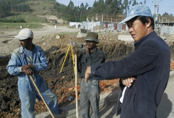 A Chinese construction worker (R) supervises the building of a road on 30 April 2007 in Makenisa, 9km south of Addis Ababa, Ethiopia. (Simon Maina/AFP)