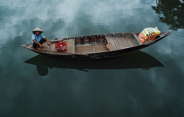 A boat and its occupant reflected in calm blue waters in Hoi An, Vietnam on June 11, 2014. (ilya/Flickr)