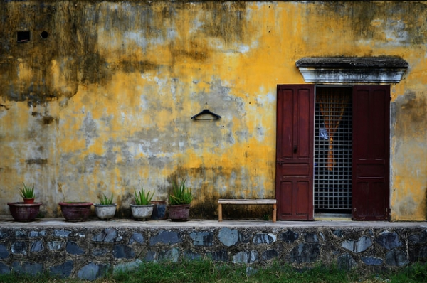 A lone hanger hangs off a decaying yellow wall in Hoi An, Vietnam on September 11, 2014. (Claire Backhouse/Flickr)