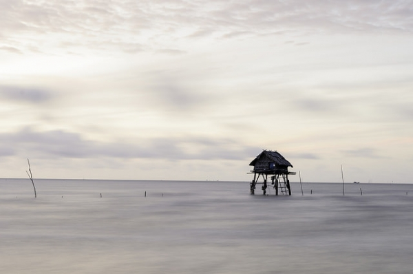 A lone house stands on poles in the water near Cần Giờ district in Vietnam on September 14, 2014. (Thanh Nam/Flickr)