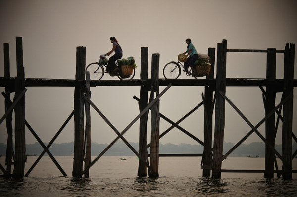 Two people cycle their way across the U Pain Bridge, built over 2000 years ago, in Mandalay, Myanmar on October 10, 2014. (Rajesh_India/Flickr)